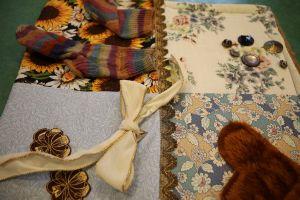 Eine fertige Nesteldecke mit Socken, Knöpfen, einer Schleife und einem Stück Fell.