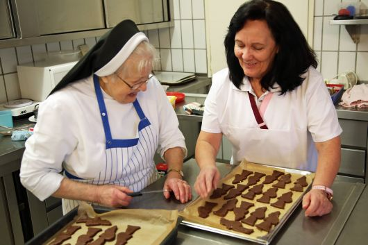 Schwester Arnolda (links) und Monika Breitenbach, Leiterin der Hauswirtschaft kümmern sich um die Lebkuchen-Nikoläuse.