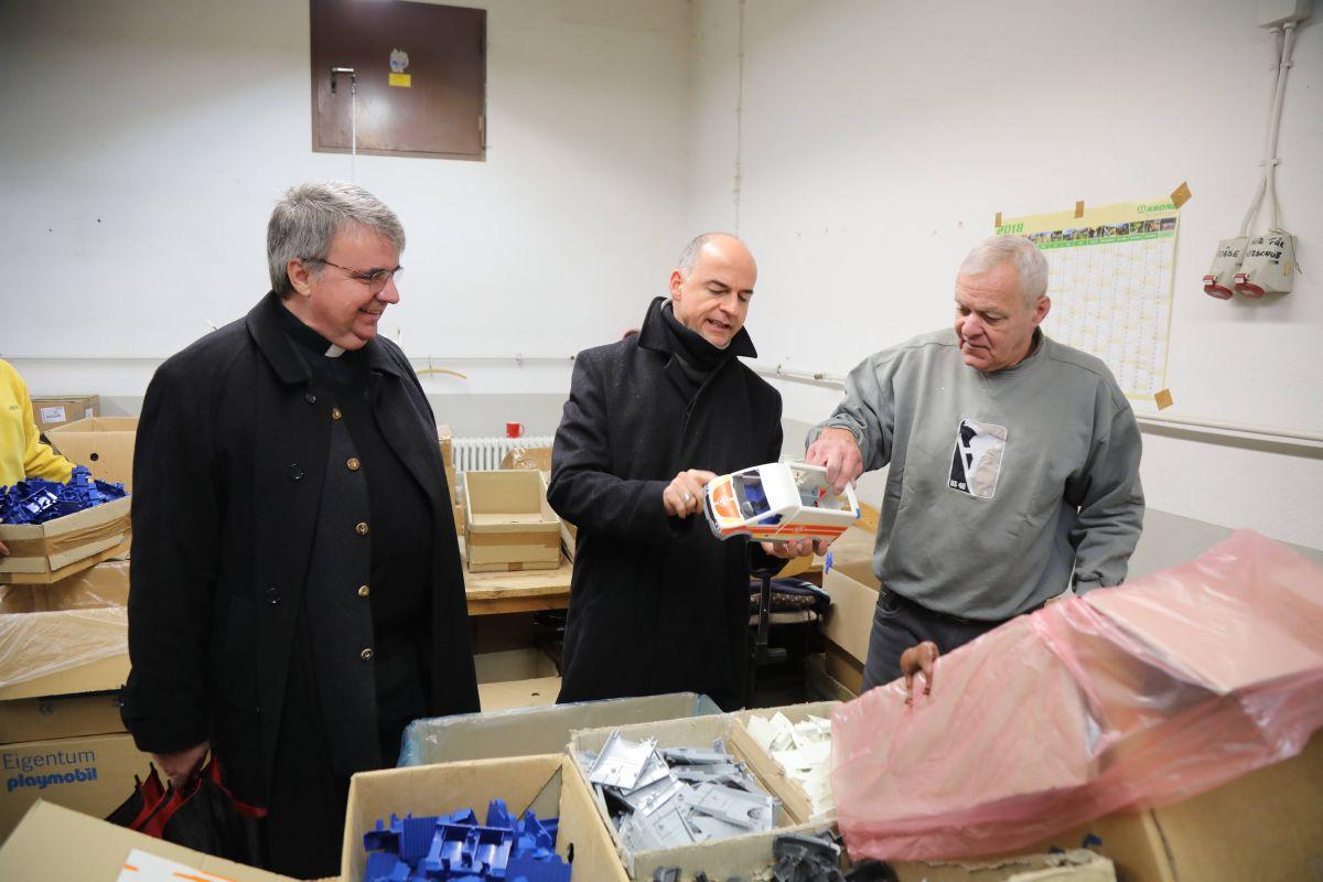 Beim Besuch auf dem Heimathof Simonshof ließ sich Bischof Dr. Franz Jung (Mitte) unter anderem die Montage eines Fahrzeugs für den Spielzeughersteller Playmobil erklären. Links Domkapitular Clemens Bieber, Vorsitzender des Diözesan-Caritasverbands Würzburg.