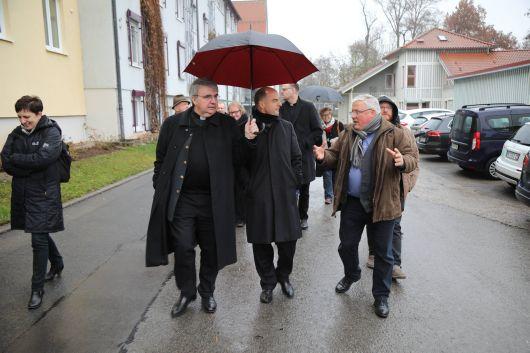 Albrecht Euring (rechts), Leiter des Simonshofs, führte Bischof Dr. Franz Jung (Mitte) durch die Einrichtung. Domkapitular Clemens Bieber sorgte dafür, dass der Regen nicht den Bischof erwischte.