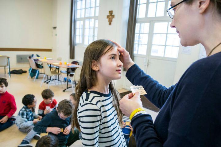 Eine Katechetin segnet ein Mädchen während eines Katechismusunterrichts am 13. November 2018 in Paris. An der Wand im Klassenraum hängt ein Kruzifix.