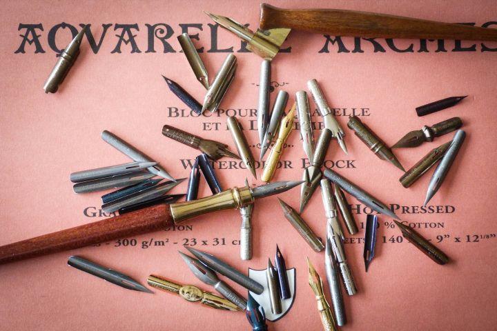 Unterschiedliche Kalligrafie-Federn (Spitzfedern, Ellenbogenfedern, Doppelstrichfedern, Kugelspitzfedern) liegen auf einem Blatt Papier am 5. November 2017 in Wachtberg.