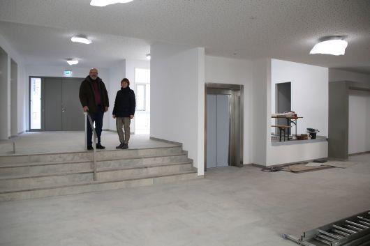 Dekan Oswald Sternagel (links) steht mit Martina Bausenwein, Mitglied der Kirchenverwaltung, im großen Eingangsbereich. Der Aufzug neben ihnen ermöglicht zu allen Etagen des Pfarrzentrums einen barrierefreien Zugang.