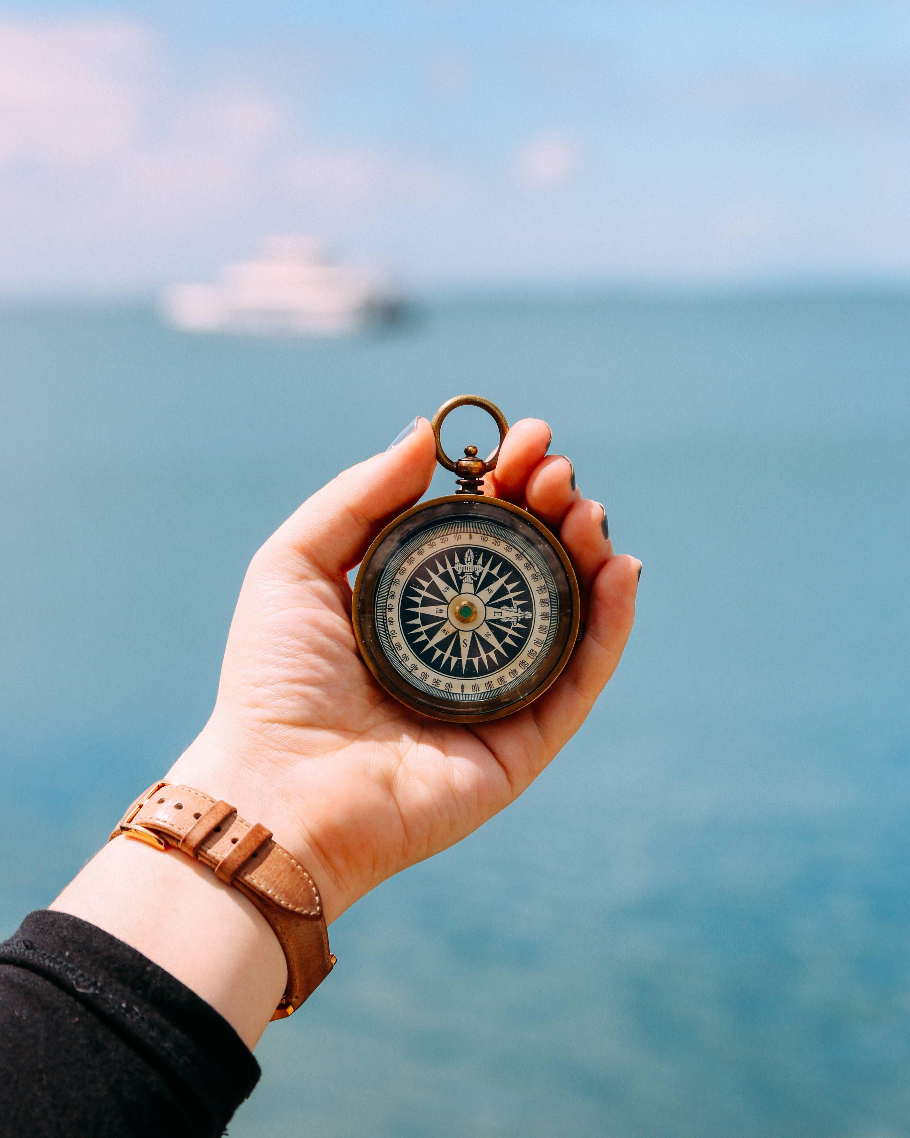 Eine Person hält am Meer einen Kompass in der Hand. Am Horizont ist ein Schiff zu sehen.