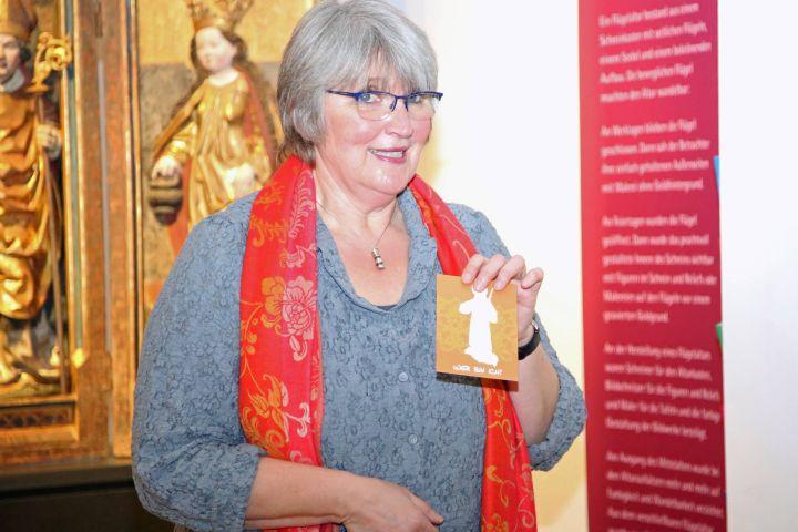 Der Kilians-Altar aus dem Historischen Museum Basel ist als Leihgabe im Museum für Franken in Würzburg zu sehen: Museumsleiterin Dr. Claudia Lichte mit einer Postkarte zur Ausstellung. Darauf wird ein Heiliger aus dem Kilians-Altar vorgestellt.