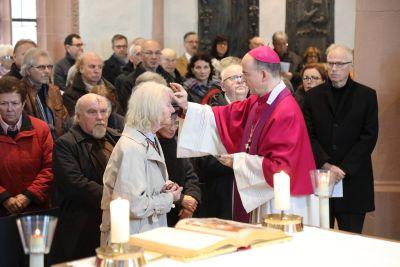 Bischof Dr. Franz Jung legt beim Aschermittwoch der Künstler in der Sepultur des Würzburger Kiliansdoms den Menschen das Aschenkreuz auf.