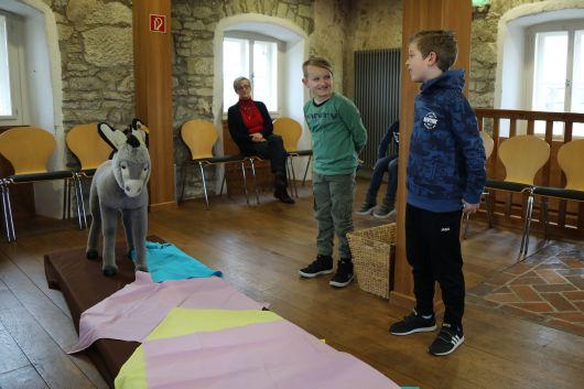 Zu Beginn der Führung durch den Ostergarten in Haßfurt stehen die Kommunionkinder Fabian (Mitte) und Julien (rechts) aus Gerolzhofen an einem Weg, der den Weg nach Jerusalem darstellen soll.