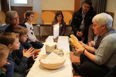 So wie Jesus das Brot mit seinen Freunden teilte, teilt Angelika Reinhart (rechts) das Brot mit den Kommunionkindern und stellt im Ostergarten im Bibelturm in Haßfurt das Passahfest nach.