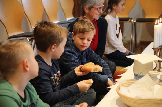 Fabian reißt sich ein Stück vom Brot ab und gibt es an Julien weiter. Erst wenn jeder ein Stück bekommen hat, isst die Gruppe das Brot in absoluter Stille.