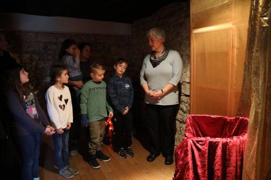 Die Kommunionkinder stehen vor dem Stuhl von Pontius Pilatus, der über Jesus ein Urteil fällen soll.