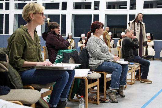 Regisseur Paul Kroth (rechts, sitzend) beobachtet aufmerksam die Probe. Die Zahl der Helfer hinter der Bühne - von Technik über Regieassistenz bis zu Souffleusen - ist fast genauso groß wie die der Schauspieler.