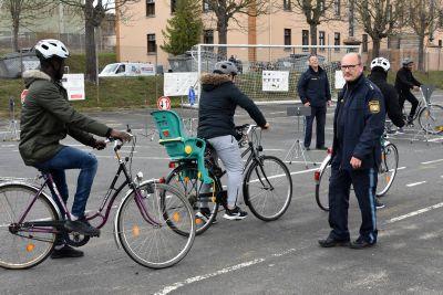 Fahrradtraining für Geflüchtete in der Gemeinschaftsunterkunft: Die Beamten Elmar Heinrich (vorne rechts) und Wolfgang Hartmann (vierter von rechts) von der Polizeiinspektion Würzburg-Stadt geben Einblick in die Straßenverkehrsordnung.