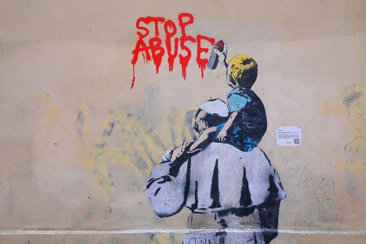 """Ein Graffito des Straßenkünstlers TVBOY zeigt Papst Franziskus von hinten und ein Kind auf seinen Schultern in der Vicolo degli Osti in Rom am 23. März 2019. Der kleine Junge sprüht in roter Farbe die Aufschrift """"Stop Abuse"""" an die Hauswand."""