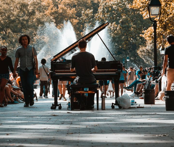 Ein Mann spielt im Washington Square Park in New York vor einer Fontäne Klavier.