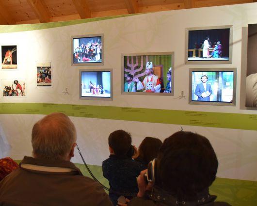 Besucher vor einer Wand im Museum, an der auf verschiedene Bildschirmen die Geschichte der Sömmersdorfer Passionsspiele gezeigt wird.
