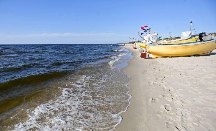"""Gelbe Fischboote am Strand der Frischen Nehrung an der Ostsee in Polen am 8. Juni 2015. Neben den Booten sind Fußspuren im Sand zu sehen. Dieses Bild ist Teil der Bildreportage """"Frisches Haff und Nehrung"""" der Katholischen Nachrichten-Agentur (KNA)."""