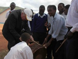 Den Menschen im tansanischen Partnerbistum Mbinga war Bischof em. Dr. Paul-Werner Scheele sehr zugewandt. Das Foto zeigt ihn 2011 bei einem Besuch in der Sekundarschule von Kigonsera. Auf Einladung der Schüler versucht er sich als Trommler.