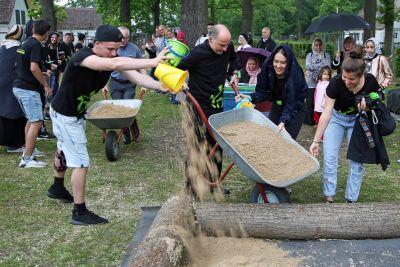 Bischof Dr. Franz Jung hilft beim Befüllen des neuen Sandkastens in der Gemeinschaftsunterkunft Corlette Circle in Kitzingen.