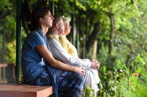 Gläubige am 19. November 2015 auf dem Meditationsplatz des christlichen Ashrams Sameeksha in Kalady im südindischen Kerala. Die Frauen und Männer sitzen mit geschlossenen Augen im Grünen und meditieren.