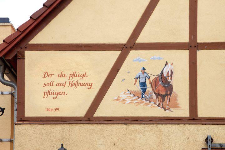 """Zu sehen ist das Bild eines mit einem Pferd pflügenden Bauers am Scheunengiebel im Archehof in Klosterbuch an der Freiberger Mulde in Sachsen am 31. Mai 2012. Hinzugefügt ist ein Satz aus dem Neuen Testament, zu finden im Ersten Korintherbrief 9.9 (""""Der da pflügt, soll auf Hoffnung pflügen"""")."""