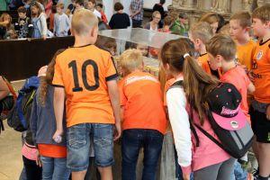 Kommunionkinder betrachten die Häupter der Frankenapostel Kilian, Kolonat und Totnan.