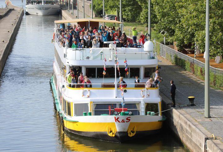 Mit dem Schiff kommen rund 250 Gläubige aus dem Dekanat Ochsenfurt in Würzburg an. Vom oberen Deck winken die Kommunionkinder den Passanten auf der Alten Mainbrücke zu.