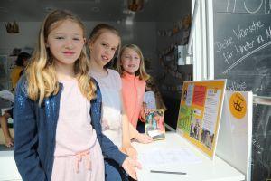 Marie, Julia und Lea (von links) stehen an der Station mit den Informationen über die Sternsingeraktion.