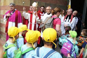 Bischof Dr. Franz Jung besprengt die Kinder an der Pforte des Doms mit Weihwasser.