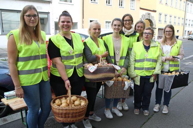 Helfer verteilen nach der Statio in Sankt Burkard Brötchen an die jungen Pilger.