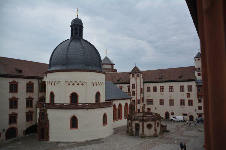 Die Würzburger Marienkirche (oben) – nicht zu verwechseln mit der Marienkapelle am Marktplatz – steht im Innenhof der Hauptburg (unten), bestehend aus dem Fürstenbau (Ostflügel), dem Bibliotheks- und Hofstubenbau (Südflügel), dem Alten Zeughaus (Westflügel) und der Schottenflanke (Nordflügel).