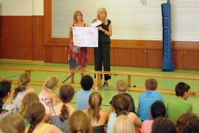 Schulrektorin Angelika Stauf (links) übergab in der Turnhalle der Volksschule Elisabethenheim in Würzburg an DAHW-Bildungsreferentin Maria Hisch den Spendenscheck.