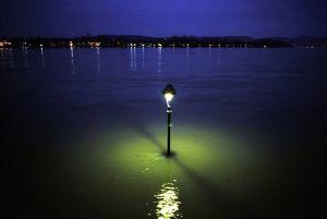 Hochwasser im Januar 2003 in Bonn. Gespenstisch leuchten die im Wasser stehenden Laternen der Rheinpromenade.