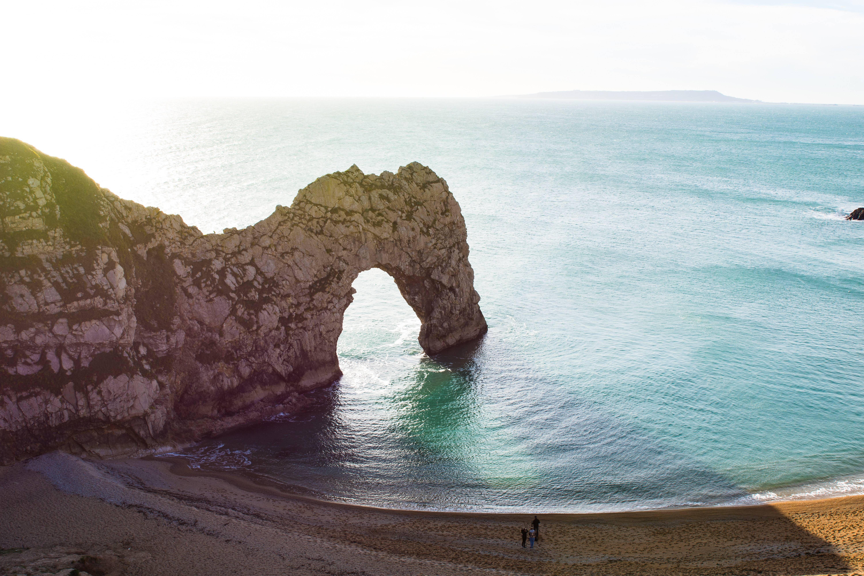 Blick auf die Felsbrücke Durdle Door. Die Gesteinsformation aus Kalkstein befindet sich an der bekannten Jurassic Coast, einem von der UNESCO als Weltnaturerbe ausgezeichneten Abschnitt der Südenglischen Kreideküste.