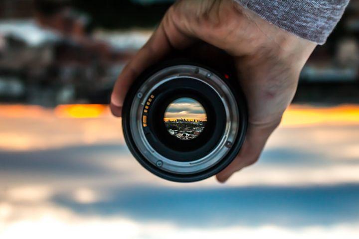 Eine Person hält in ihrer Hand die Linse einer Kamera, durch die die Silhouette einer Stadt zu sehen ist.