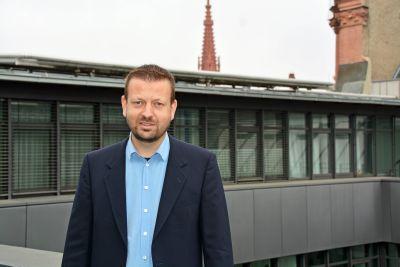 """""""Beim Thema Photovoltaik haben wir noch viel Potenzial."""" Umweltbeauftragter Christof Gawronski steht auf dem Balkon des Kilianshauses. Im Hintergrund sind die Photovoltaikanlagen auf dem Dach zu sehen."""