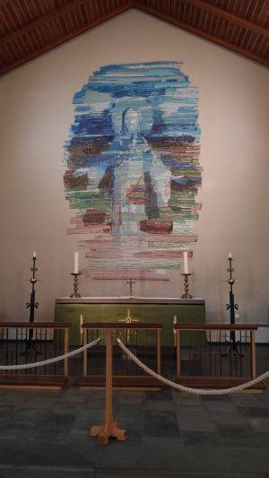 Der Altarraum der Kirche des Ortes Skalholt, Island, mit einem Wandgemälde, auf dem Jesus Christus zu sehen ist.