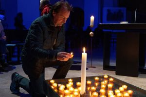 """Ein Teilnehmer der """"Moonlight Mass"""" entzündet eine Kerze."""