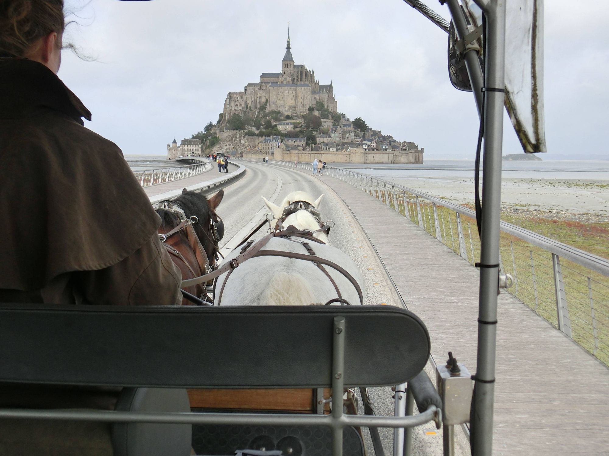 Gemächlichen Schritts ziehen der Schimmel Cesar und sein Kumpel die Kutsche mit den Besuchern über die Brücke – dem beeindruckenden Mont-Saint-Michel vor der Küste Frankreichs entgegen.