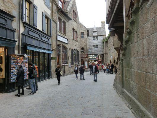 """Hinter den Eingangstoren des Mont-Saint-Michel erstreckt sich die """"Grande Rue"""" (französisch: große Straße), die – verglichen mit Straßen auf dem Festland – doch eher schmal daher kommt."""