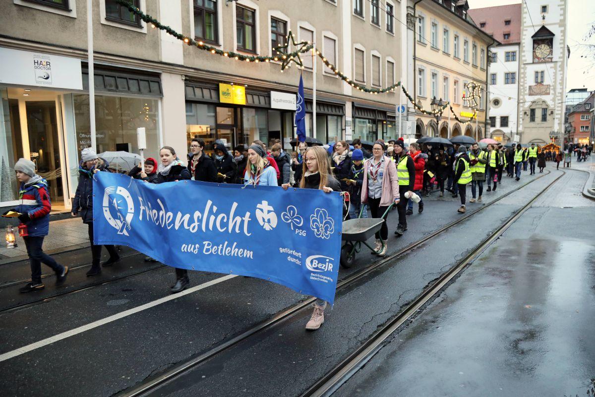"""Vom Vierröhrenbrunnen führte der """"Weg-Gottesdienst"""" zur Sankt-Ursula-Schule. An der Aussendungsfeier nahmen rund 100 Menschen teil."""
