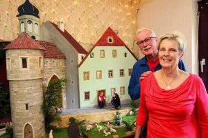 """Das Ehepaar Gisela und Bruno Steger vor der ersten Großkrippe, die der 70-Jährige vor rund  20 Jahren gebaut hat. Sie stellt das 1870 abgerissene Stadttor von Gerlozhofenund die historische Gaststätte """"Zur Traube"""" dar."""