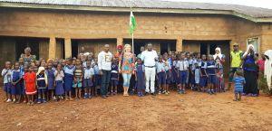 Schüler und Lehrer vor der aktuellen Schule mit (Mitte von links) Ortspfarrer Frederick Idih, Silvia Friedrich und Pfarrer Dr. Blaise Okpanachi.