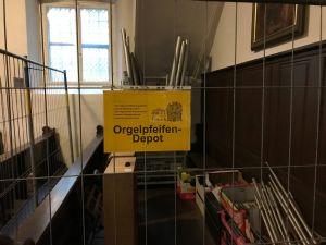 Die einst der Größe nach sorgfältig drapierten Orgelpfeifen lagern nun hinter Bauzäunen verschlossen unterhalb der wuchtigen Orgelempore. Dort können sie nach jedem Gottesdienst gegen eine Spende erworben werden.