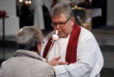 Ein Priester beim Erteilen des Blasiussegens.