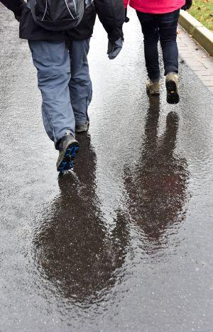 Fastenkurs im Kloster Waldbreitbach: Fastende wandern gemeinsam in Regenkleidung auf einem Feldweg. Ihre Schatten spiegeln sich auf der nassen Straße.