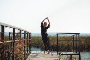 Eine Frau tanzt bei Sonnenlicht auf einem erhöhten Holzweg zwischen Geländerbrüstungen.