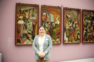 """Museumspädagogin Dr. Yvonne Lemke vor den Bildtafeln mit der Kilianslegende in der Sonderausstellung """"Riemenschneider X Stoss"""". Die satten Farben, prächtigen Muster und liebevollen Details sollen bei den Teilnehmern Erinnerungen wecken oder Emotionen auslösen."""