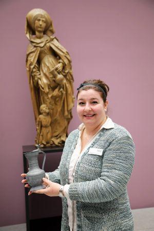 Museumspädagogin Dr. Yvonne Lemke mit einem Krug aus dem Museumsdepot, ähnlich dem, den die Figur der heiligen Elisabeth im Hintergrund in der Hand hält. Sie hofft, dass es die Erinnerungen der Teilnehmer weckt, wenn sie manche Stücke auch anfassen können.