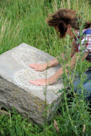 Eine Wandergruppe auf den Spuren des Heiligen Augustinus auf einem Feld nahe Messelhausen am 24. Juni 2012. Am Feldrand liegt eine große Skulptur mit einem Herzen, eine Frau berührt sie mit beiden Händen. Die Gruppe wandert auf dem Augustinusweg.