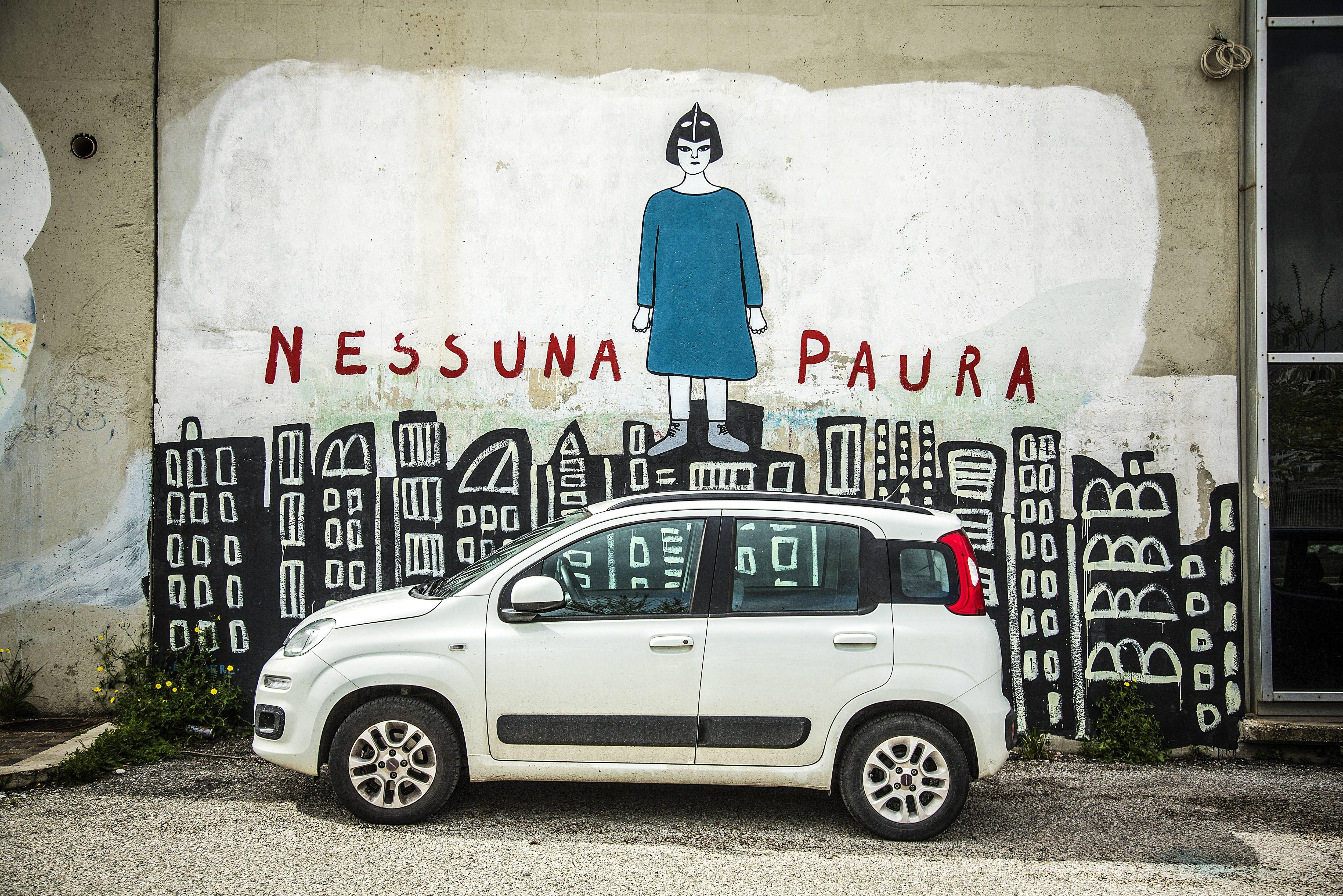 Ein weißes Auto parkt vor einer Mauer, die zum 960 Meter langen, zehngeschossigen Wohnkomplex Nuovo Corviale gehört, auch Riesenschlange genannt, am 4. April 2018 in Rom. Über dem Graffito auf der Mauer steht